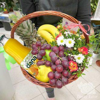 Фрукты, цветы и напиток в корзине